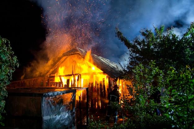 Maison en bois ou grange en feu la nuit.