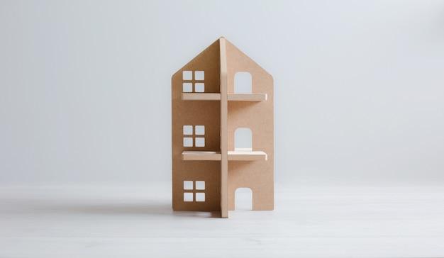 Maison en bois jouet sur plancher en bois blanc et fond clair.
