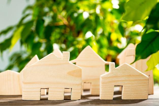 Maison en bois jouet sur table en bois sur fond de feuillage