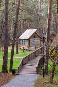 Maison en bois avec un manoir dans la forêt. la maison a peint windows. un pont en bois mène à la maison de l'autre côté de la rivière.