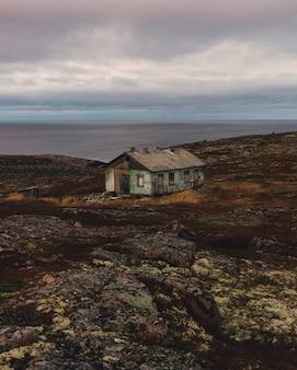 Maison en bois marron sur champ brun sous des nuages blancs et ciel bleu pendant la journée