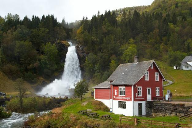 Maison en bois norvégienne traditionnelle et cascade au loin