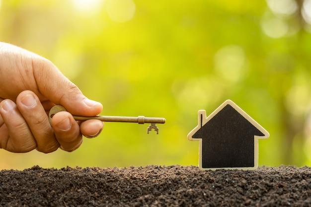 Maison en bois poussant dans le sol et clé vintage sur fond de flou de nature verte. clé du succès du concept de croissance d'entreprise à domicile