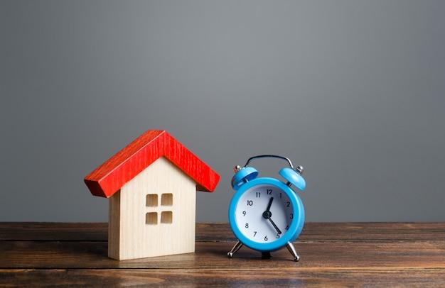 Maison en bois et réveil. concept d'hypothèque et de prêt.