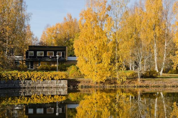 Maison en bois sur le rivage parmi les arbres d'automne