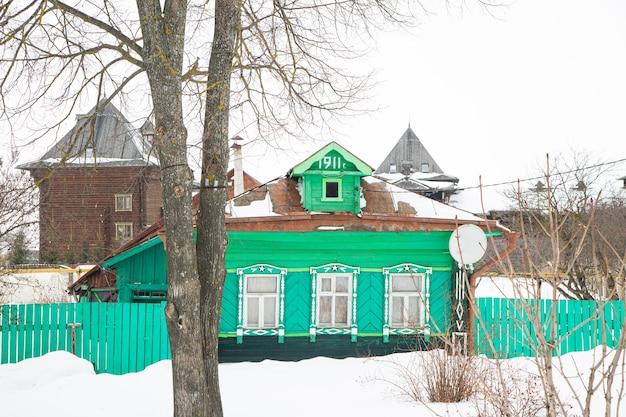 Une maison en bois russe couverte de neige