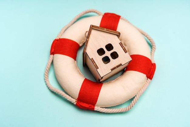 Maison en bois se trouve dans une bouée de sauvetage. concept d'aide à l'achat de biens immobiliers