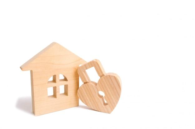 Maison en bois avec serrure en forme de coeur sur fond blanc.