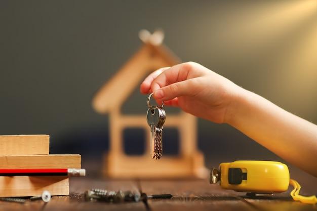 Maison en bois sur une surface en bois à partir de planches et un tas de clés avec une puce. concept - construction de maison clé en main. photo de haute qualité