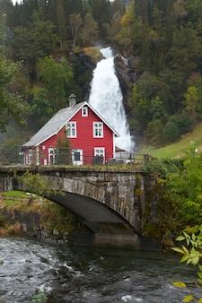 Maison en bois traditionnelle norvégienne et vieux pont en arc avec cascade au loin