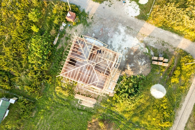 Maison en brique inachevée avec structure de toit en bois en construction.