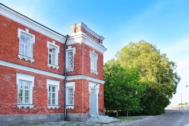Maison en brique rouge avec cadres blancs sur les fenêtres et arbre vert sous ciel bleu, rue d'été
