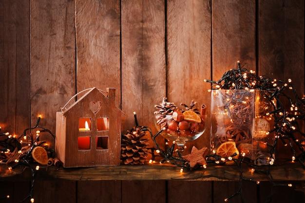 Maison brune avec bougie et guirlande électrique sur bois