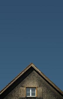 Maison brune et grise sous un ciel bleu pendant la journée