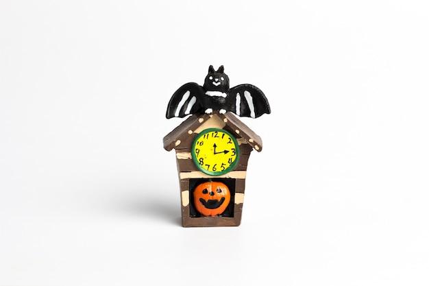 Maison brune halloween avec une citrouille, une montre jaune et une chauve-souris noire sur le toit.