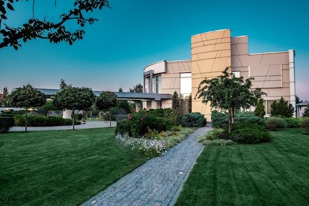 Maison de campagne moderne et espace vert attenant bien entretenu avec chemin pavé au soleil du matin