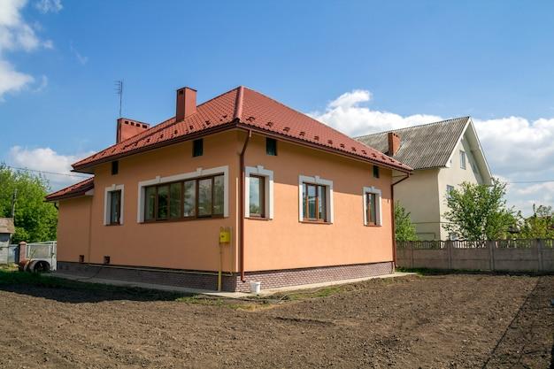 Maison de campagne neuve à un magasin avec toit en tuiles rouges, fenêtres en plastique, murs en plâtre et hautes cheminées