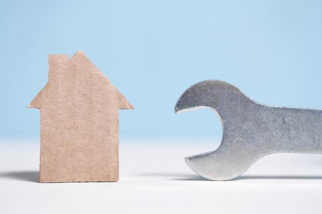 Maison en carton abstraite à côté d'une clé. r