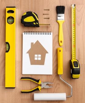 Maison en carton sur un bloc-notes et des outils