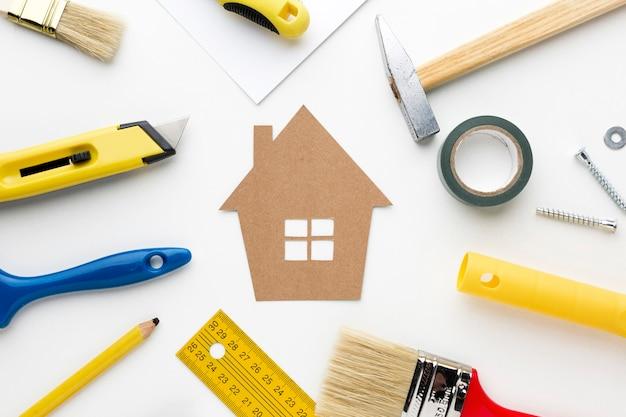 Maison en carton entourée d'outils de réparation