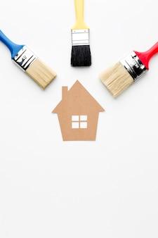 Maison en carton et pinceaux de réparation de peinture