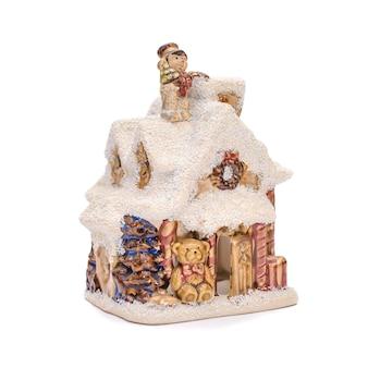 Maison en céramique de noël avec toit d'hiver couvert de neige et un ours sur fond blanc