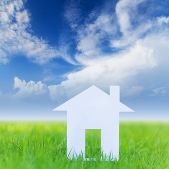 Maison sur un champ vert avec un ciel bleu