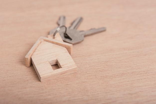 Maison clé sur fond de table en bois.