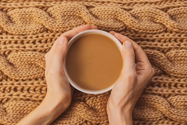 Maison confortable nature morte : tasse blanche avec café, mains féminines, écharpe en grosse maille. notion d'hiver. nuances chaudes, gros plan.