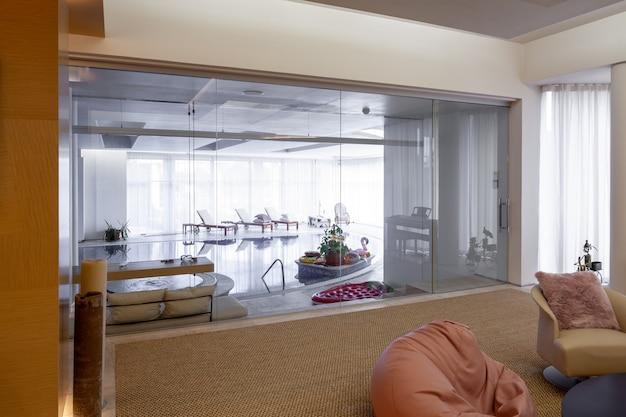 Maison confortable avec piscine intérieure séparée par un mur de verre du salon