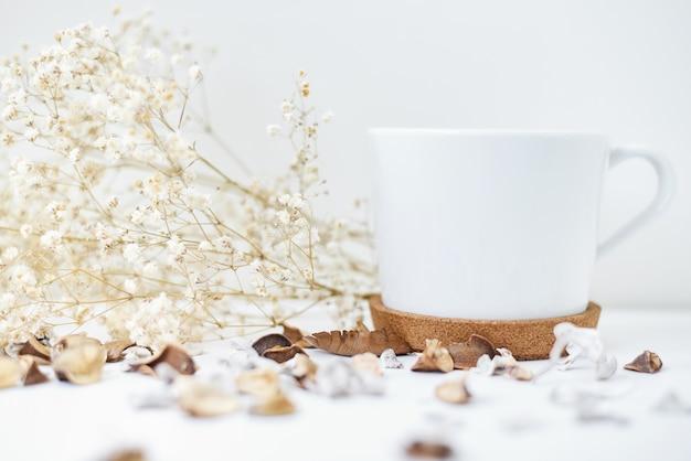Maison confortable avec une tasse de café et une branche de fleurs. hygge style hiver ou automne