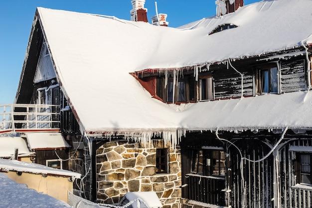 Maison couverte de neige dans des conditions hivernales difficiles.