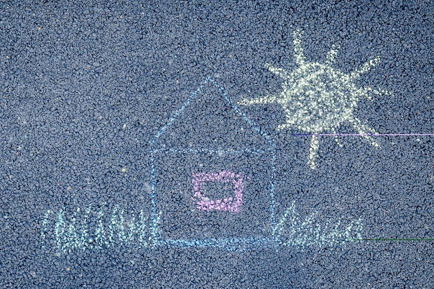 Maison de crayons de craie de couleur peinte, soleil et herbe sur l'asphalte