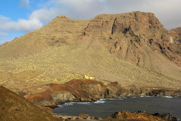 Maison dans les rochers. baie dans les montagnes, éclairée par le soleil