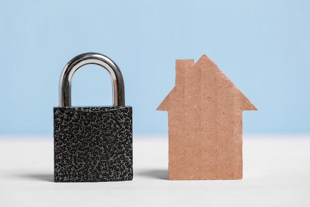Maison découpée en carton et cadenas noir sur bleu et blanc.