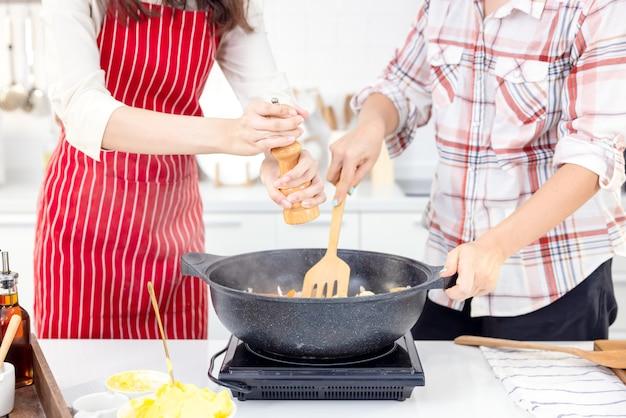 A la maison, deux potes s'amusent en cuisine. des sœurs préparent ensemble des spaghettis dans la cuisine. dans la cuisine, deux copines