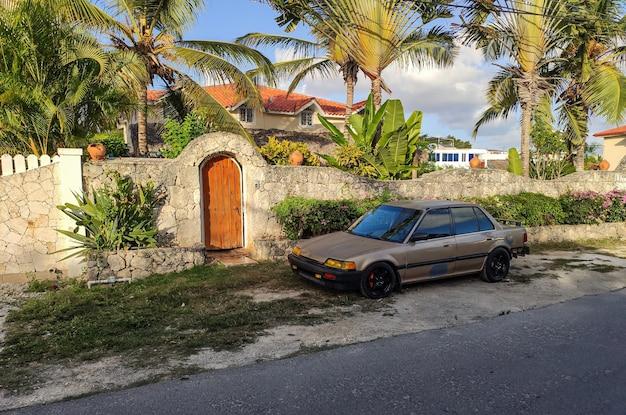 Maison dominicaine avec une voiture devant la maison et une palme qui cerate décoration un contraste avec le ciel bleu