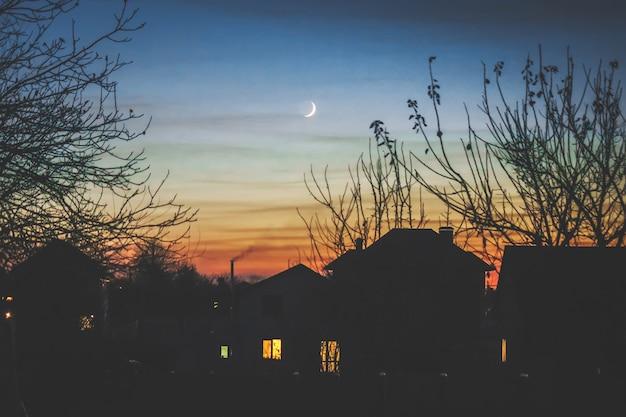 Maison du soir à l'ombre et au jeune mois.