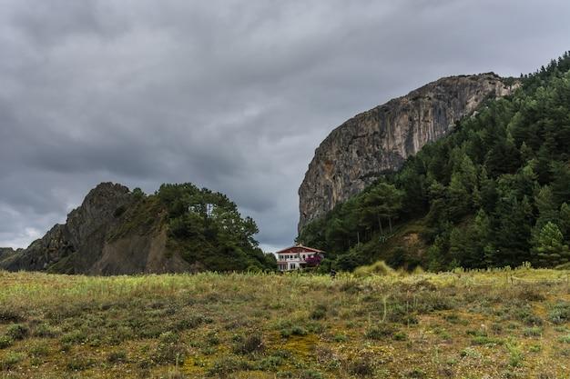 Maison entre collines, une crête et un ciel orageux