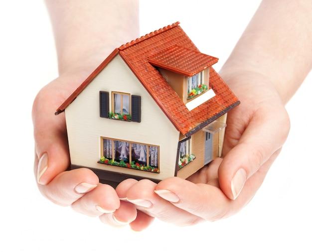 La maison entre des mains humaines