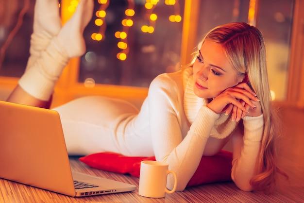 La maison est le meilleur endroit au monde. belle jeune femme en pull blanc et chaussettes allongé sur le sol et regardant un ordinateur portable avec des lumières de noël en arrière-plan