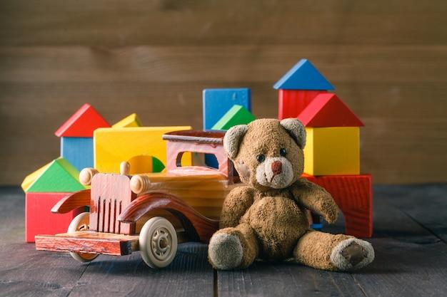 Maison faite de blocs de bois à assembler, près d'atoy et d'une petite voiture en bois