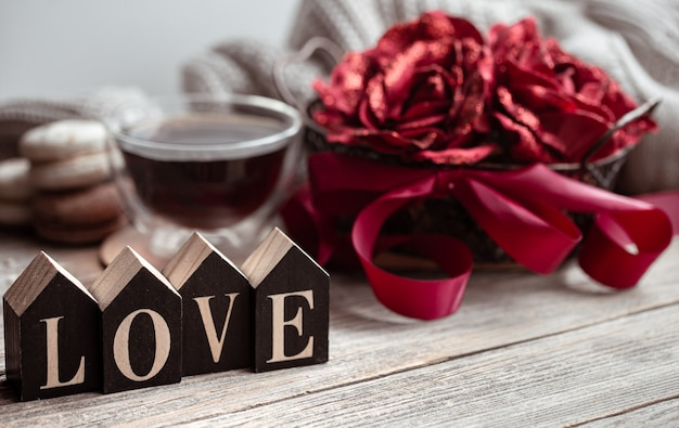 Maison de fête nature morte avec mot en bois amour, une tasse de thé et de fleurs