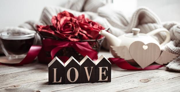 Maison de fête nature morte avec mot en bois amour, une tasse de thé et une théière sur un arrière-plan flou.
