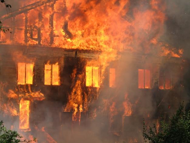 Maison en flammes, grand bâtiment en bois complètement détruit par un incendie