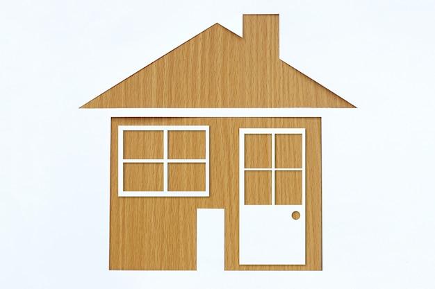 Maison en forme de papier sur un fond de bois brun.