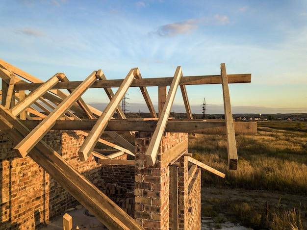 Maison d'habitation privée avec charpente en bois en construction. bâtiment en brique inachevé en cours de développement.