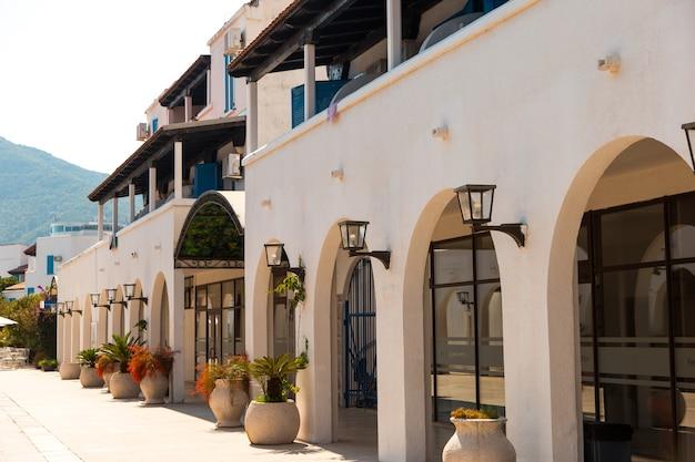 Maison, hôtel de style grec, murs blancs, arcades et fleurs en pots.