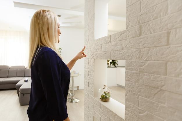 Maison intelligente. belle femme joyeuse regardant le panneau sensoriel tout en appuyant dessus