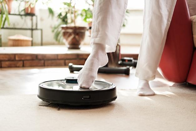 Maison intelligente, pied comprend aspirateur robot, concept de vie paresseux et confortable